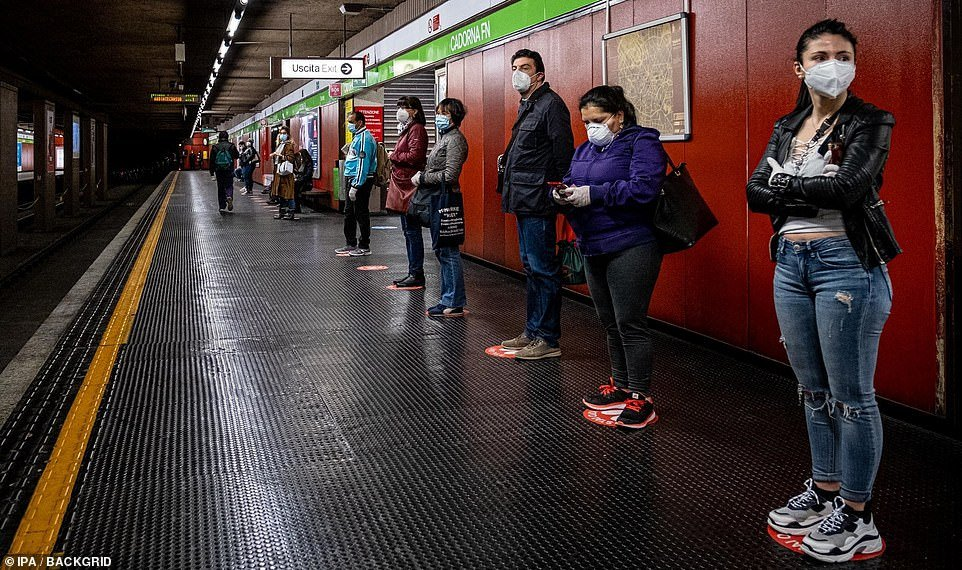 Milan metro passengers stand on designated spots to enforce a 3ft safety distance as they wait for their train today