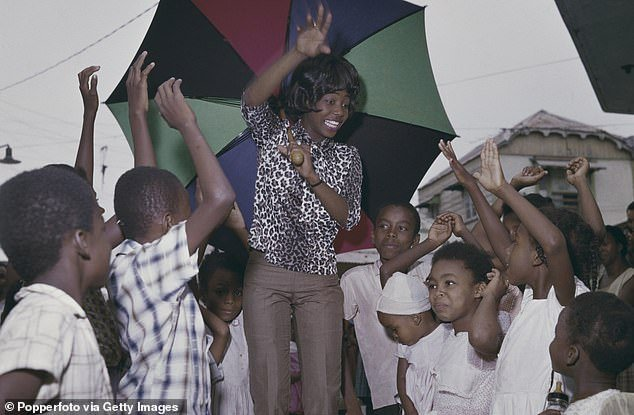 The Jamaican singer, who had an international hit with My Boy Lollipop, pictured holding a large umbrella while stood with children during her tour of Jamaica around 1966