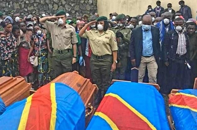 Military personnel salute over the coffins of the Virunga national park rangers last month