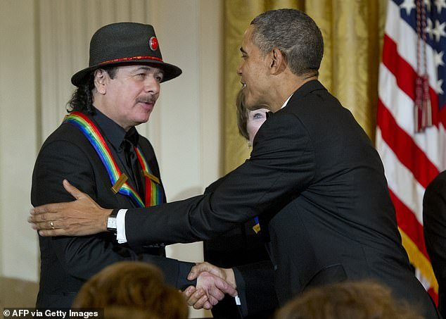 Praised: US President Barack Obama shakes hands with Kennedy Center Honoree musician Carlos (L) during a reception for Kennedy Center Honors reception at the White House in Washington in 2013