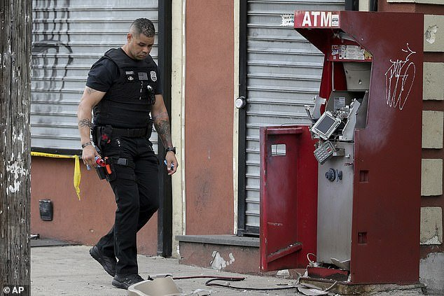 A member of the Philadelphia bomb squad surveys the scene after an ATM machine was blown-up at 2207 N. 2nd Street in Philadelphia, Tuesday