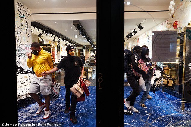 Monday marked the worst night for looting in NYC with 2,330 stores burglarized. People are pictured inside a Dolce & Gabbana store in Soho, Manhattan on Monday