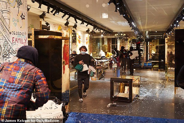 Looting suspects are seen carrying items from the D&G store that was targeted after the Black Lives Matter protests around the city on Monday