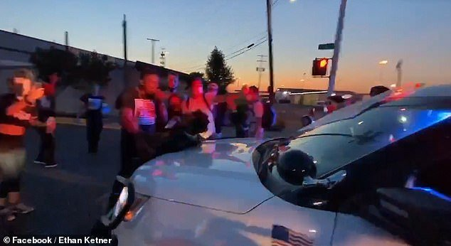 In a clip - believed to be taken yesterday evening - a large crowd of protesters can be seen gathered around the front of a Detroit Police vehicle while chanting