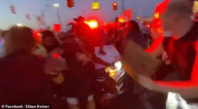 Suddenly, the car surges forward into the group of poster-clutching demonstrators who scream as they get out the way
