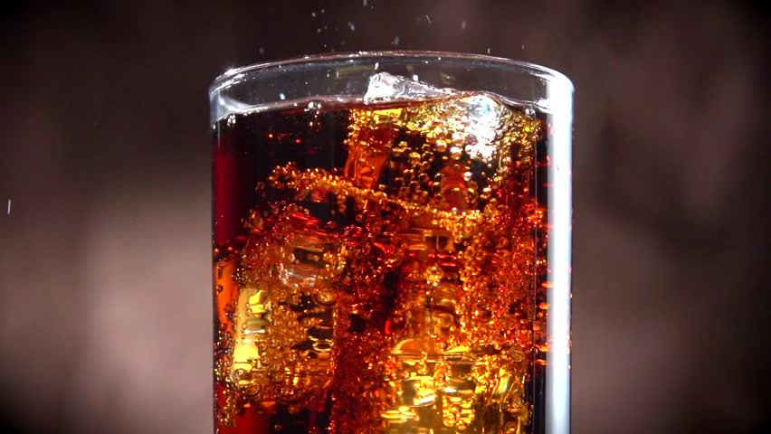 Cola with ice. Pouring Cola with Ice and bubbles in glass. Soda ...