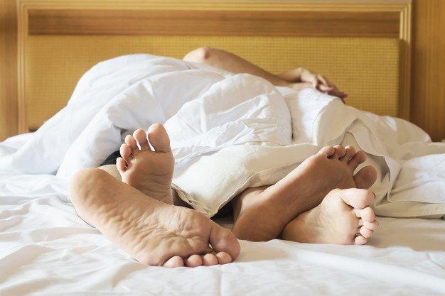 Pareja en cama blanca en habitación de hotel foco a pies   Foto Gratis
