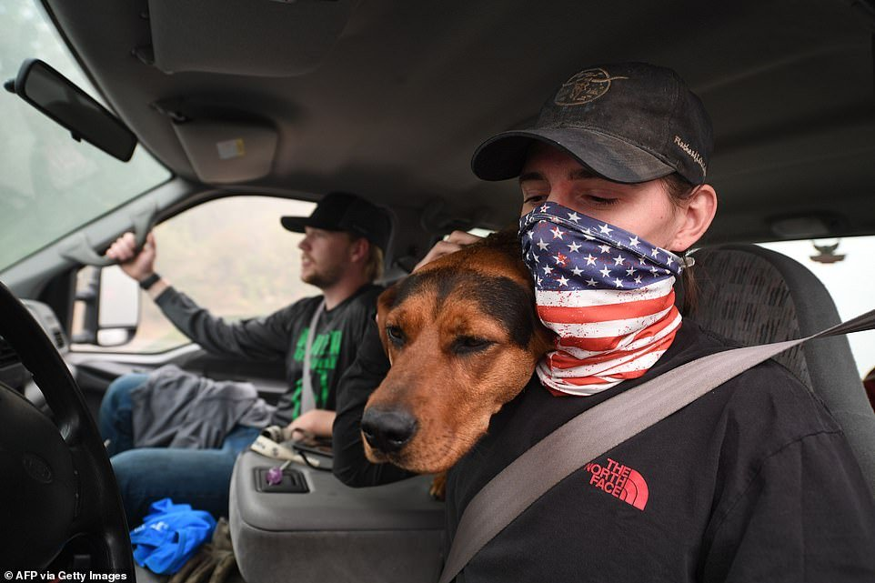 James Smith hugs his dog Rose after returning to his evacuated home to find looters had stolen his motorcycles in Estacada, Oregon, on Saturday