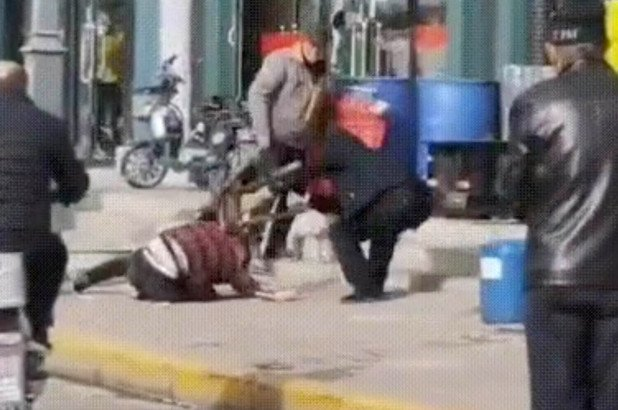 A man appears to beat a woman in the streets of Shuozhou in China.