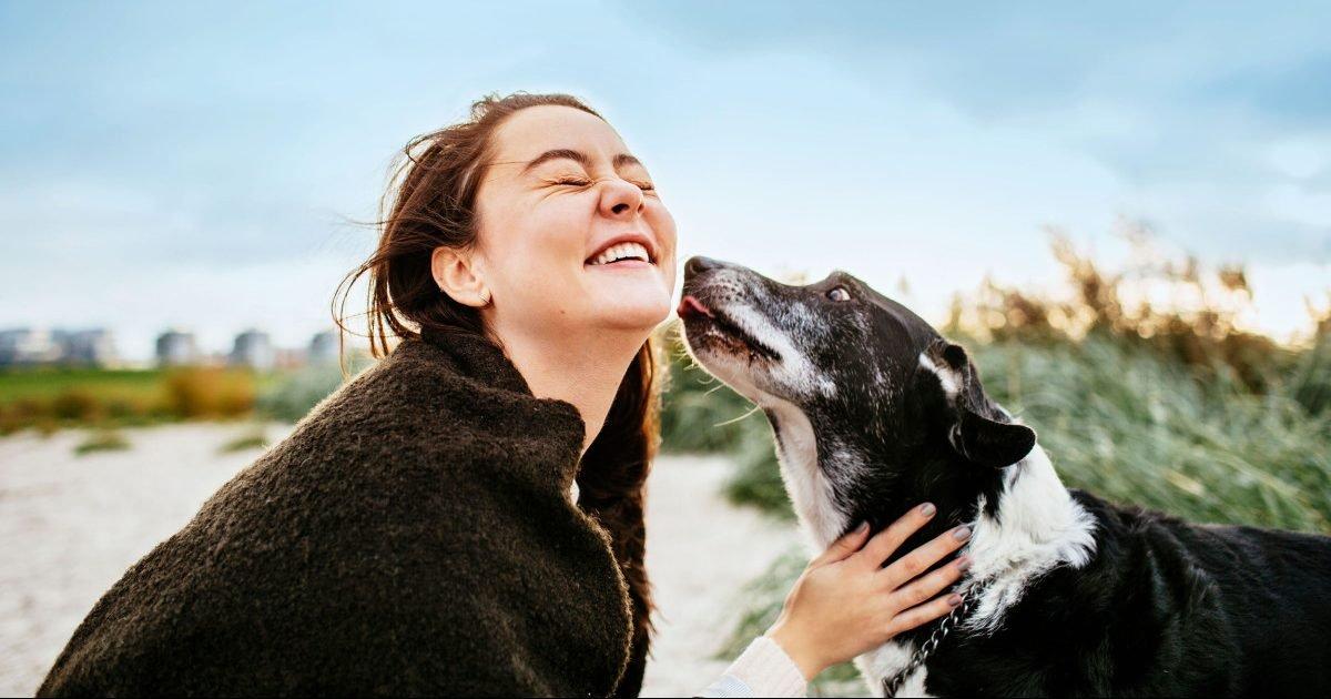 girl smiling with dog getty 661789463 e1606416456283.jpg?resize=412,232 - La perte d'un chien peut être plus difficile que celle d'un proche
