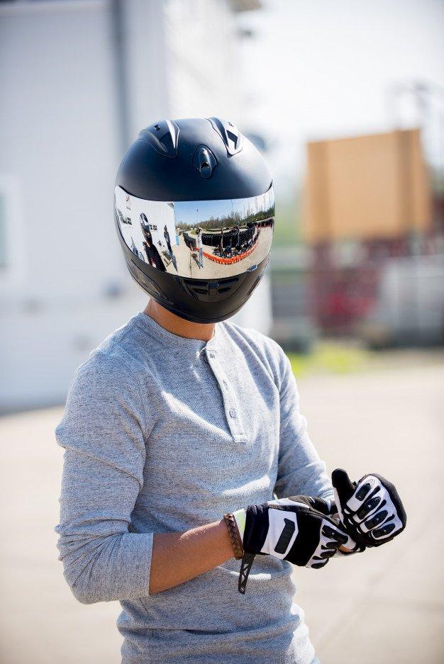 오토바이 헬멧을 착용하는 사람의 세로 샷 | 무료 사진