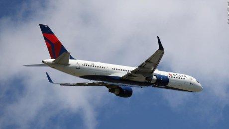 2 pasajeros con un perro abren puerta de avión en movimiento de Delta