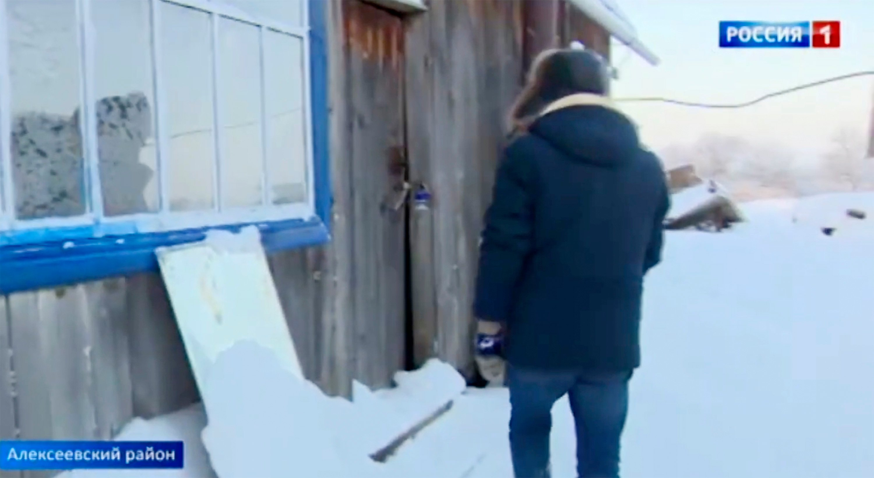 Journalist stands in front of the abandoned house where the boy was found