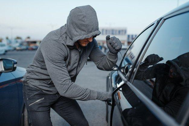 자동차 도둑이 도어록을 깨고, 범죄 행위, 강도. 두건이있는 남성 강도 오프닝 차량 주차. | 프리미엄 사진