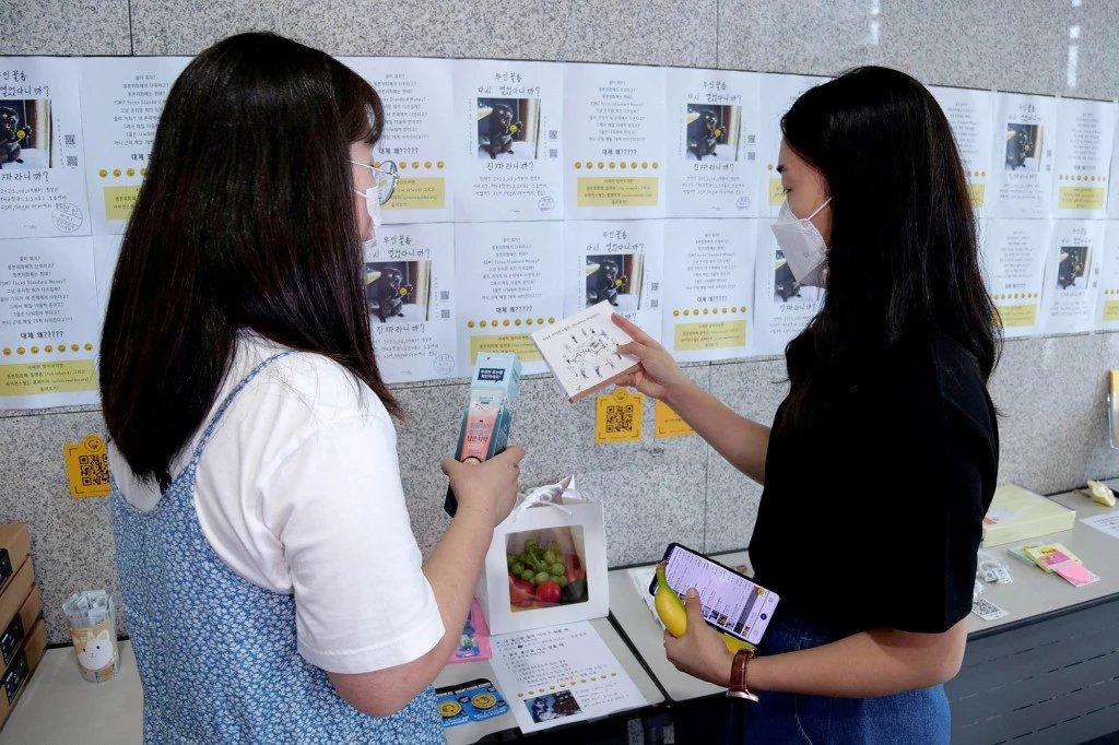 """""""꿀""""을 적립받은 UNIST 학생들이 교내 대변 화폐시장에서 물품을 살펴보고 있다 / 뉴욕포스트"""