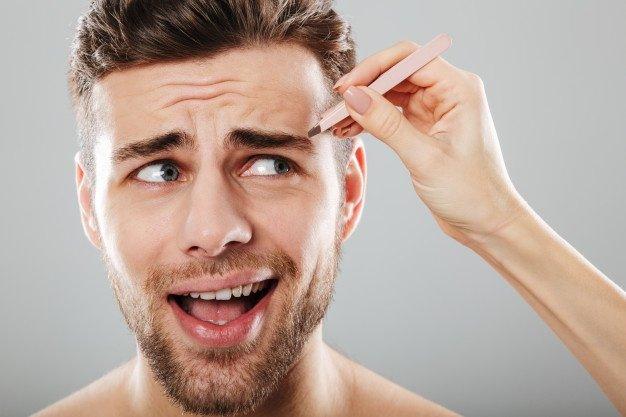 Mão feminina arrancar as sobrancelhas dos homens assustados Foto gratuita