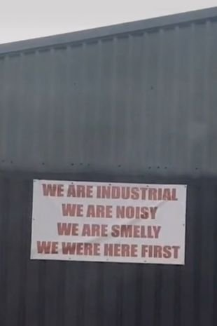 """The sign warns residents: """"We are industrial. We are noisy. We are smelly. We were here first."""""""