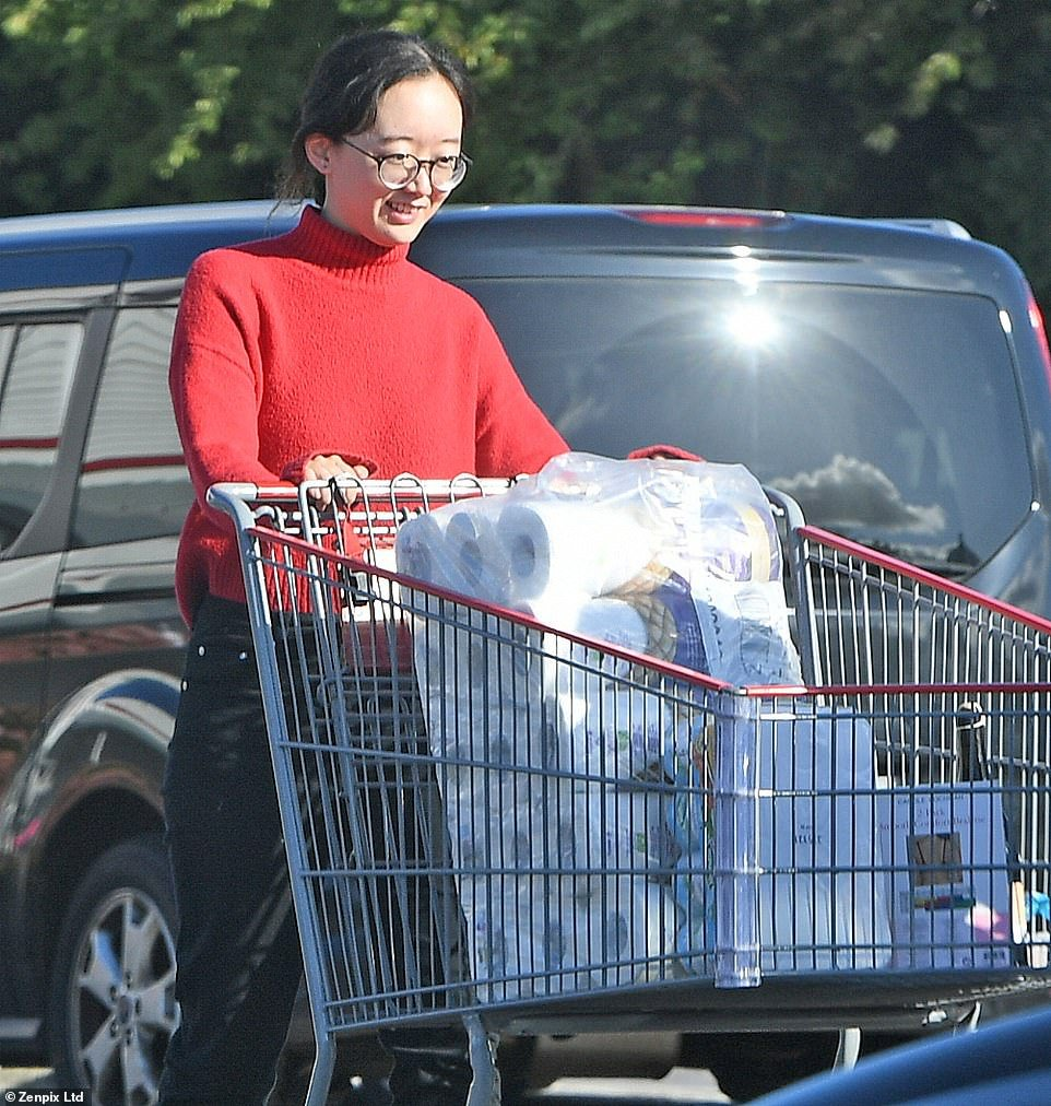 A female panic-buyer can be seen pushing a trolley as he leaves a Costco store in Manchester full of toilet roll