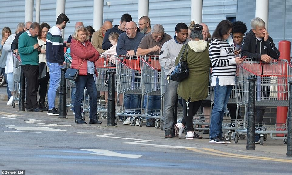Panic-buyers queued outside a Costco store in Manchester early this morning to stock up on essential items