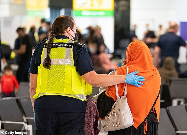 Afghan families who fled to Britain during the Taliban takeover of their country have asked to be sent back home. Pictured:Border Force staff assist a female evacuee as Afghan refugees arrive from Kabul at Heathrow Airport
