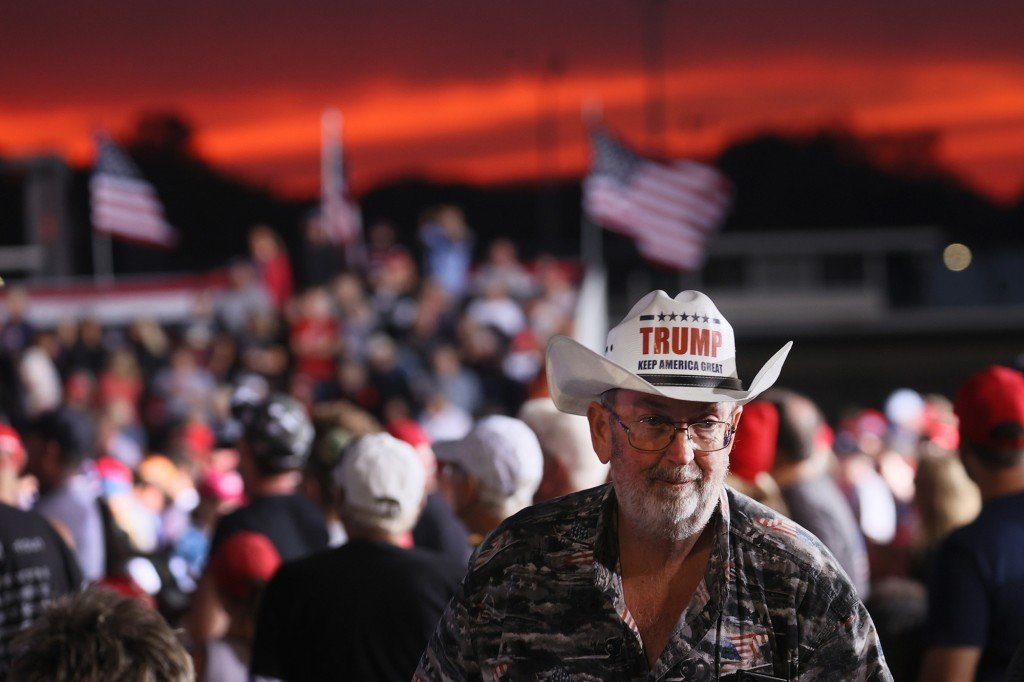 """A supporter dons a """"Trump Keep America Great"""" cowboy hat during former President Donald Trump's rally at the Iowa State Fairgrounds."""
